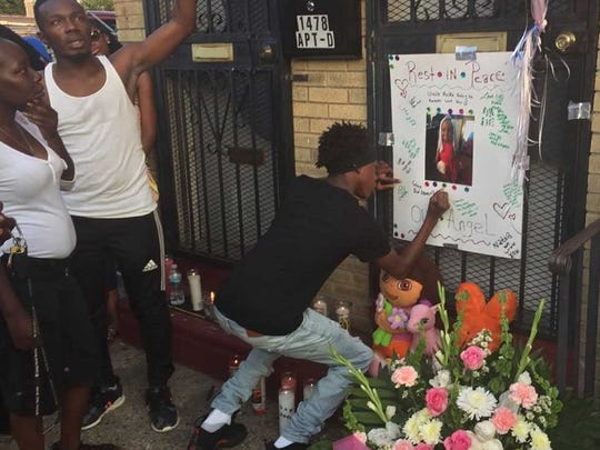 Tyreon Thompson, 15, signs a memorial poster for Natalise Gunter, a slain Camden child.