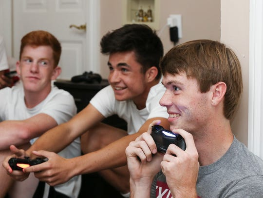 Carter Alvey, 17, right, plays video games at the home