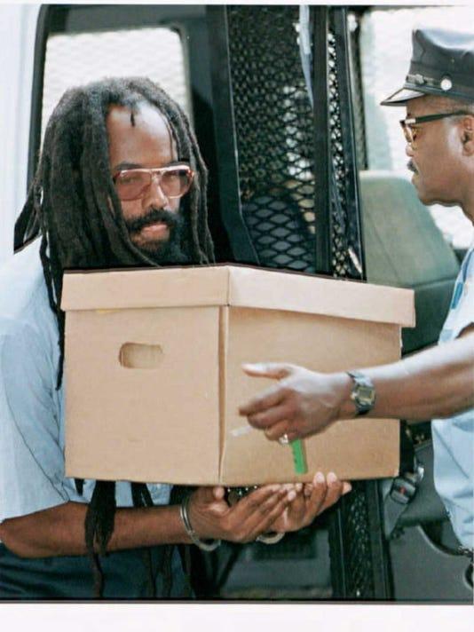 Mumia Abu-Jamal carries 02 August a box of legal d