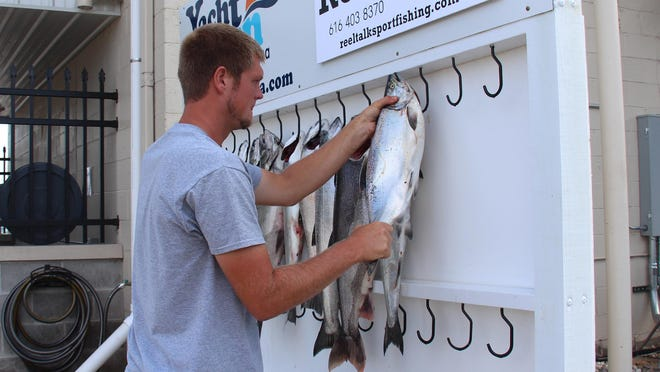 Captain Nick Everse hangs up fish after a charter fishing excursion on August 14, 2017, in Holland. Charter fishing, whose economic impact can surpass $25 million in a good year, is one of the businesses arguably hit hardest by the closures.