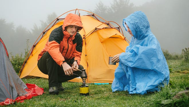 Tourists cooking coffee on primus near the tent in the mountains. Foggy and rainy camping while hiking.
