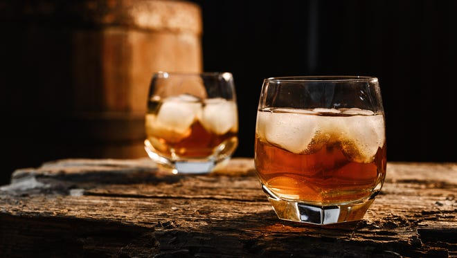 A glass of whiskey with ice on a wooden background close-up, in the background of a barrel of whiskey