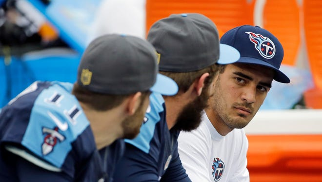 Injured Tennessee Titans quarterback Marcus Mariota, right, sits on the bench with quarterbacks Alex Tanney (11) and Zach Mettenberger in the second half of the game against the Houston Texans. The Texans won 34-6.