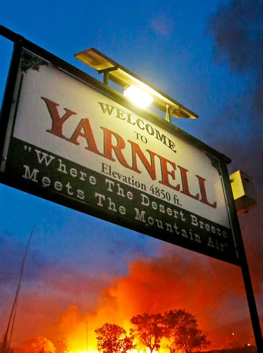 "The Yarnell Hill Fire burns structures behind the  ""Welcome to Yarnell"" sign."