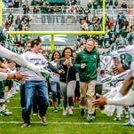 MSU football head coach Mark Dantonio, right, and MSU students run onto the field through a gauntlet of MSU football players prior to the MSU Spring Football game Saturday.