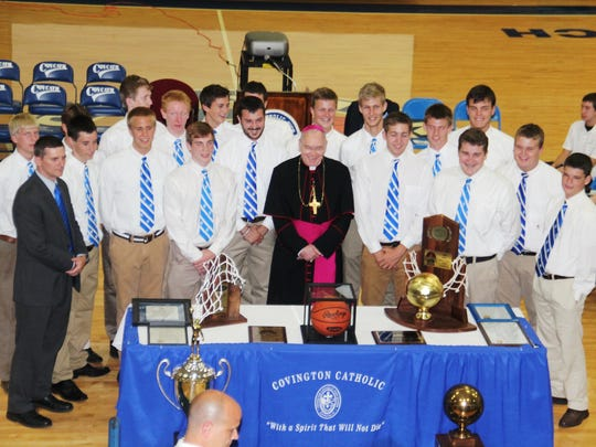 CovCath players and coaches celebrate with Covington Bishop Roger Foys. Covington Catholic presented state championship rings to its 2014 boys basketball Sweet 16 state champions Aug. 6 at the school gymnasium.