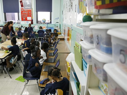 First grade students work on lessons at St. Joseph Catholic School in the West End neighborhood of Cincinnati on Tuesday, Jan. 19, 2016. St. Joseph is currently implementing the blended learning method in its school, having students split time between traditional instruction and computer programs.