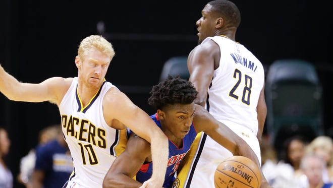 Detroit Pistons forward Stanley Johnson, middle, steals the ball from Indiana Pacers forward Chase Budinger (10) as he breaks past the pick set by Indiana Pacers center Ian Mahinmi (28)during the first half of a preseason NBA basketball game in Indianapolis, Tuesday, Oct. 13, 2015. (AP Photo/Michael Conroy)