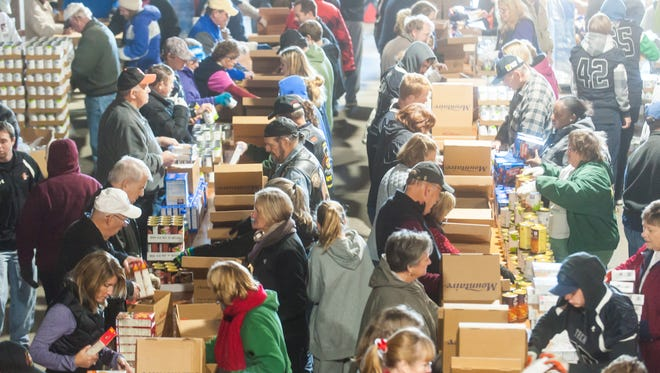 Members of the community help pack Thanksgiving boxes Monday morning at Mountaire Farms in Selbyville as part of Thanksgiving For Thousands.