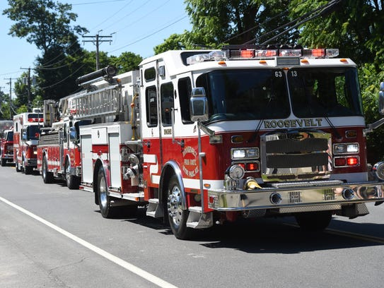 Fire trucks drive down Albany Post Road as part of