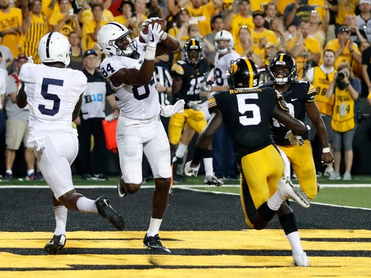 Penn State wide receiver Juwan Johnson (84) catches a touchdown pass between teammate DaeSean Hamilton, left, and Iowa defensive backs Manny Rugamba and Miles Taylor, right, as time expires in an NCAA college football game Saturday, Sept. 23, 2017, in Iowa City, Iowa. (AP Photo/Jeff Roberson)
