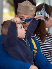 Blue Angels Pilot, Lt. Andy Talbott reconnects with his son, 2-year-old, Noah, after the team's return to Pensacola from winter training Monday afternoon.