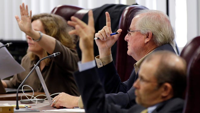 Texas Board of Education board members, from left, Donna Bahorich, David Bradley, and Thomas Ratliff, raise their hands to ask questions during a Sept. 16, 2014, public hearing for new textbooks up for adoption and use in classrooms statewide, in Austin.