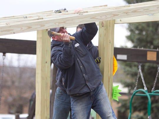 City of Brighton employee Gary Dillard wields a hammer,
