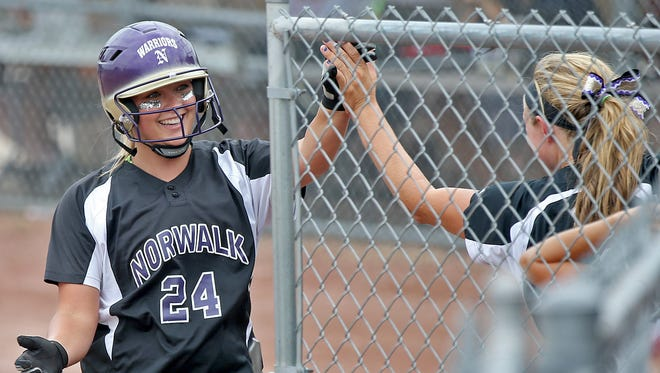 Norwalk's Sidney Zepnak, left, got a hand after scoring against West Delaware in the fourth inning in Class 4-A quarterfinal at the state softball tournament Monday.