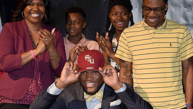 Cam Akers puts on a Florida State cap after announcing his college decision in front of his family.