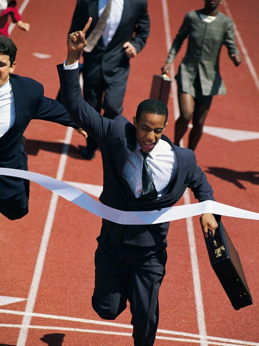 Businessman crossing finish line of race