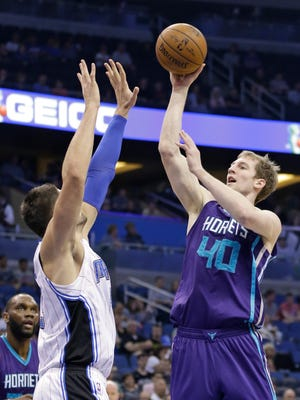 Charlotte Hornets' Cody Zeller (40) shoots over Orlando Magic's Nikola Vucevic, left, during the first half of an NBA basketball game, Sunday, March 1, 2015, in Orlando, Fla.