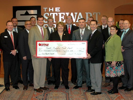 Deb Eichelberger, pictured center, executive director for the York County Food Bank, is shown accepting the $5,355 check from the Apple Automotive Group management team. Submitted