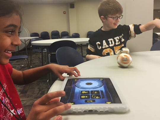 Riddhi Piyush, 7, (left) uses the iPad to control robot Sphero rotate whileColin Alexander, 10, plays with a rocket he made during Camp STEM at Volunteer State Community College in Gallatin on Tuesday, March 29, 2016.