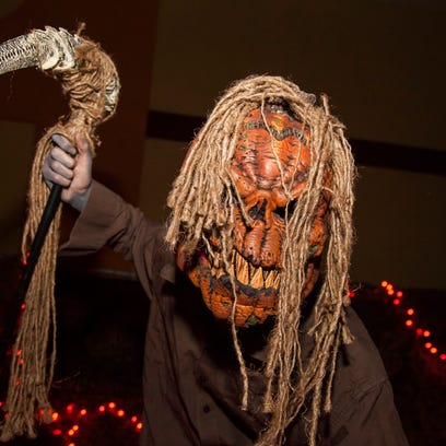 A scarer frightens visitors at Chambers of Fear Haunted