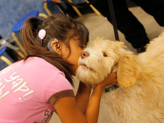 "Catalina, 10, gives ""Buddy"" a kiss during a dog training class on Monday night."