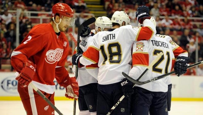 Red Wings defenseman Brendan Smith, left, skates away as the Panthers celebrate a goal by Colton Sceviour in the first period on Sunday in Detroit.