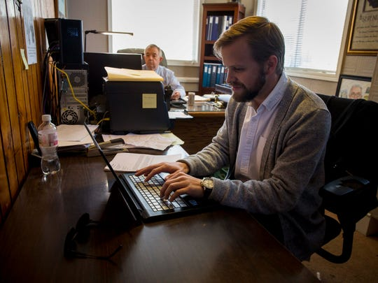 Matthew Gogerty working emails at Harbor of Hope Monday, Oct. 09, 2017.  Executive director of the recovery house, Tom Pontow, is in the background. Matthew Gogerty dropped out of high school at 16. He fell into addiction to alcohol and meth. He sold drugs. He got into trouble with the law. At one point, he was so low, he blew of his probation rules, figuring he would be better off in jail – and possibly treatment – than trying to keep on living the way he was. Now he works at the halfway house where he stayed after getting out of jail, Harbor of Hope.