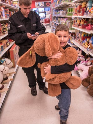 Eight-year-old Robert Hamel found the perfect stuffed companion. Canton Police Explorer Cody LaMontagne totals up Robert's purchases.