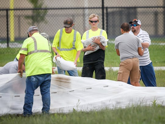 Bondurant city employees work to construct a sandbag