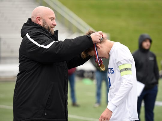 Catholic Central athletic director Aaron Babicz (left) presents the state championship medal to player Drake Midgley.