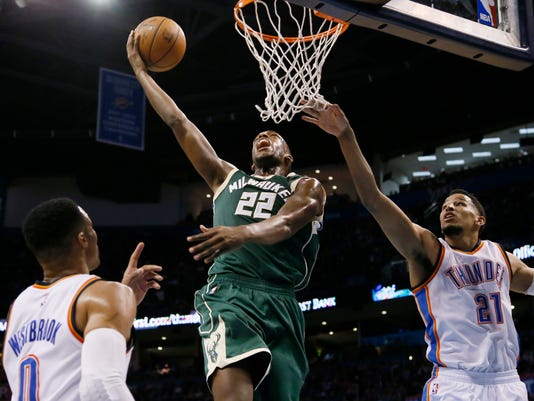 Milwaukee Bucks guard Khris Middleton (22) shoots between Oklahoma City Thunder guard Russell Westbrook (0) and forward Andre Roberson (21) in the second quarter of an NBA basketball game in Oklahoma City, Tuesday, April 4, 2017. (AP Photo/Sue Ogrocki)