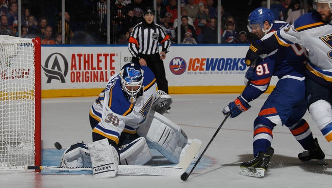 Martin Brodeur #30 of the St. Louis Blues makes the second period save on John Tavares #91 of the New York Islanders at the Nassau Veterans Memorial Coliseum on December 6, 2014 in Uniondale, New York.