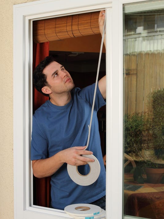 Man Installs Weather Stripping in Window