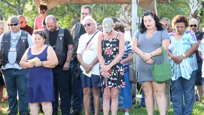Dozens of visitors to Four Freedoms Park in Cape Coral bow their heads in prayer during a vigil organized to bring members of the community together as a result of Sunday's tragedy.