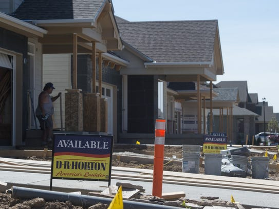 Signs advertise homes for sale as construction continues