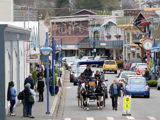 A Horse drawn carriage travels through downtown Poulsbo