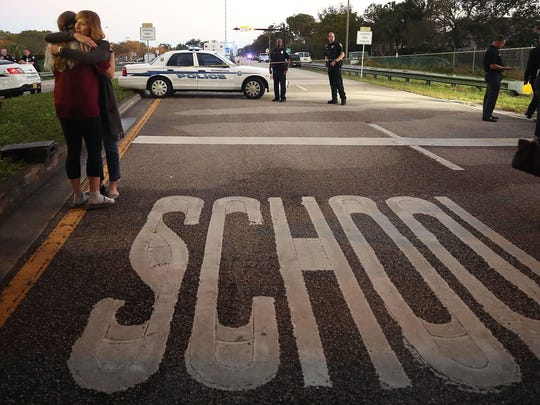 Kristi Gilroy (R), hugs a young woman at a police check point near the Marjory Stoneman Douglas High School where 17 people were killed by a gunman in Parkland, Florida.