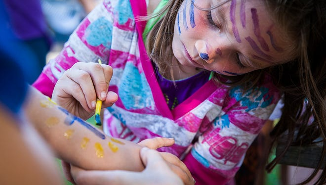 Hailey Norton takes over the face painting station while attending Union Chapel's cookout and block party at McCulloch Park in 2015.