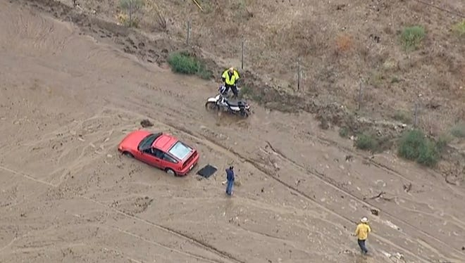 This still frame from video provided by KABC-TV shows vehicles stuck in a muddy road in the mountainous community of Lake Hughes, Calif., about 65 miles north of downtown Los Angeles. Flash flooding in northern Los Angeles County has filled several roads with mud, stranding vehicles and blocking traffic on one of the stateís main highways.