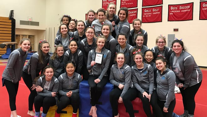 Livonia Blue's varsity girls gymnastics team celebrates following an impressive third-place finish at the Jan. 14 Lowell Invitational. The team followed that up with Wednesday's dual meet win against Canton.