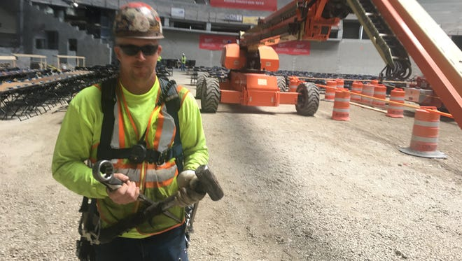 Ironworker Brandon Ladwig  bolted a ceremonial beam into place high above the Milwaukee Bucks arena during Thursday's topping off ceremony,