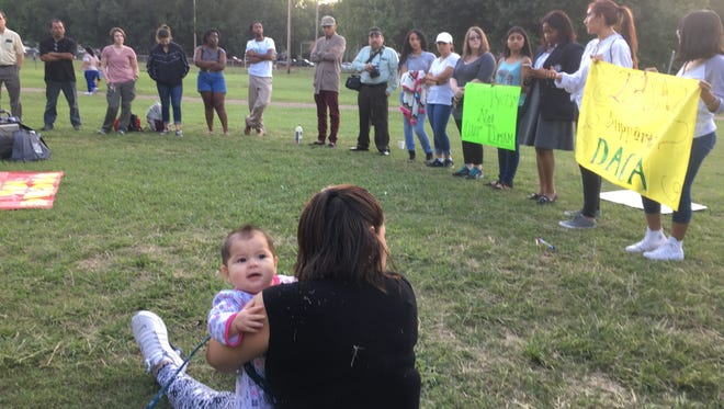 Jennifer Lujan, 32, holds her 7-month-old daughter Regina Mireles during a prayer vigil about Deferred Action for Childhood Arrivals at Gaisman Park in Berclair on September 6, 2017.