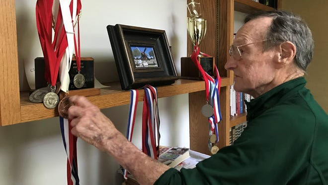 Howard Grider, 92, shows off the medals and trophies at his Okemos home that he earned when he was a downhill snow skier.