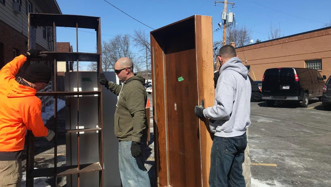 Volunteers work to move furniture out of a building slated for demolition in downtown Wausau. All the furniture will be sold at the Habitat for Humanity store in Weston.