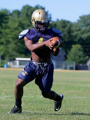 Ashante Worthy, running back runs a drill with Matthew DaSilva, quarterback, during Freehold High School football practice in Freehold, NJ Monday August 22, 2016.