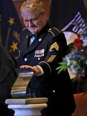 Vietnam veteran and Congressional Medal of Honor recipient Sgt. 1st Class Sammy L. Davis gently reaches to touch the Sachem Award, during the ceremony when he received the 2018 award, from Gov. Eric Holcomb, at the Indiana War Memorial, Monday, March 12, 2018.