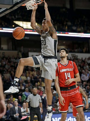 Wake Forest's John Collins (20) dunks past Louisville's Anas Mahmoud (14) during the first half of an NCAA college basketball game in Winston-Salem, N.C., Wednesday, March 1, 2017.