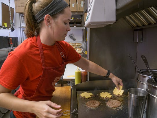 Riana Hardyniec grills cheeseburgers for a customer's