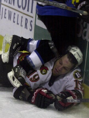 Binghamton Senators winger Brian McGrattan is pinned against the boards behind the Springfield Falcons net by the knees of the Falcons' Boyd Kane as they battled for the puck in a game in March 2003.